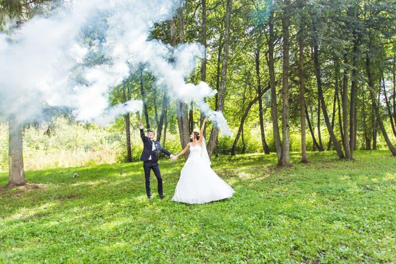 Свадьба, влюбленность, отношения, замужество Усмехаясь жених и невеста с голубым дымом стоковые изображения