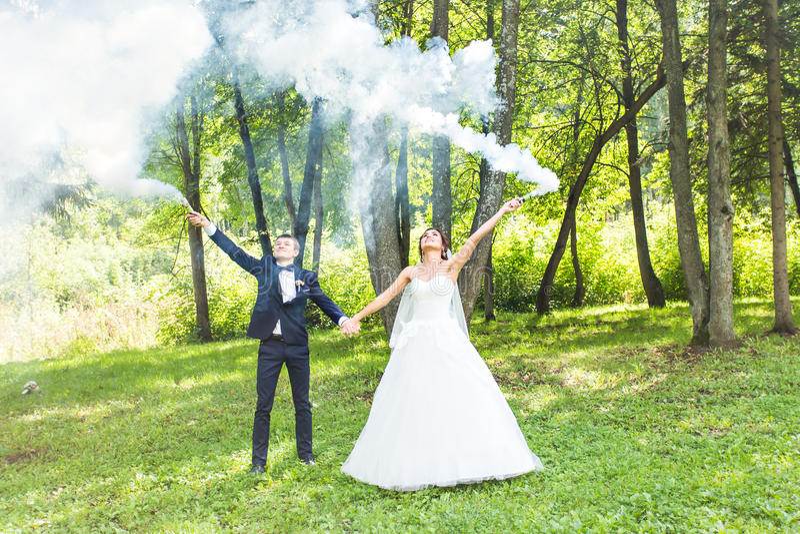 Свадьба, влюбленность, отношения, замужество Усмехаясь жених и невеста с голубым дымом стоковые изображения rf