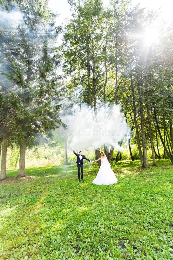 Свадьба, влюбленность, отношения, замужество Усмехаясь жених и невеста с голубым дымом стоковая фотография