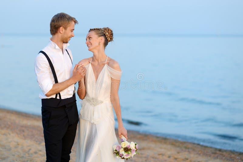 Свадьба на пляже: жених и невеста морем стоковые изображения