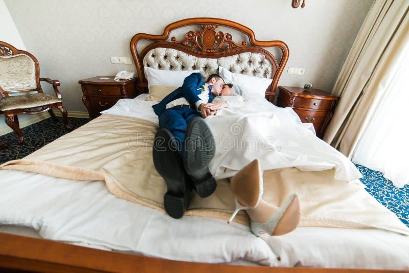 Свадьба сняла жениха и невеста лежа в стильный целовать кровати стоковые изображения