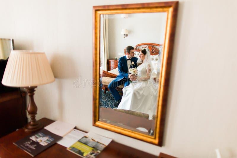 Свадьба сняла красивого жениха и невеста сидя рядом с зеркалом в гостиничном номере стоковая фотография rf