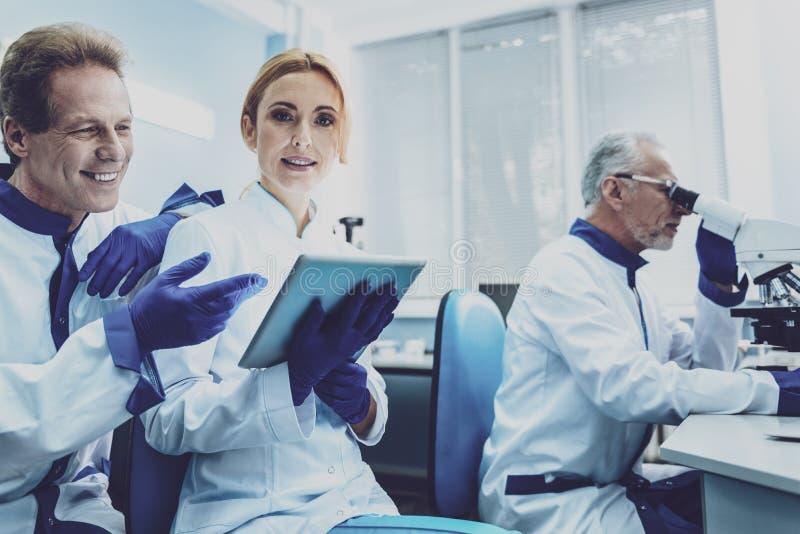 Сведущий практикующий врач работая с микроскопом стоковые фото