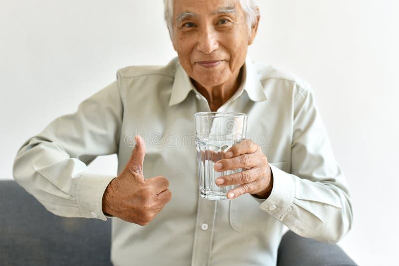 Свежая вода хорошая здоровая привычка для старика, пожилого усмехаясь азиатского большого пальца руки шоу человека до стекла очищ стоковые изображения rf