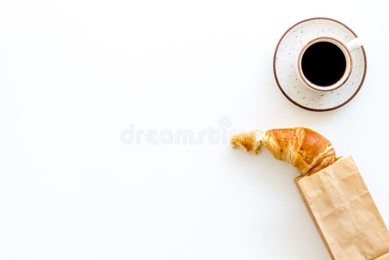Свежая выпечка с круассаном в бумажном мешке и чашке кофе на белом модель-макете взгляда сверху предпосылки стоковое фото rf