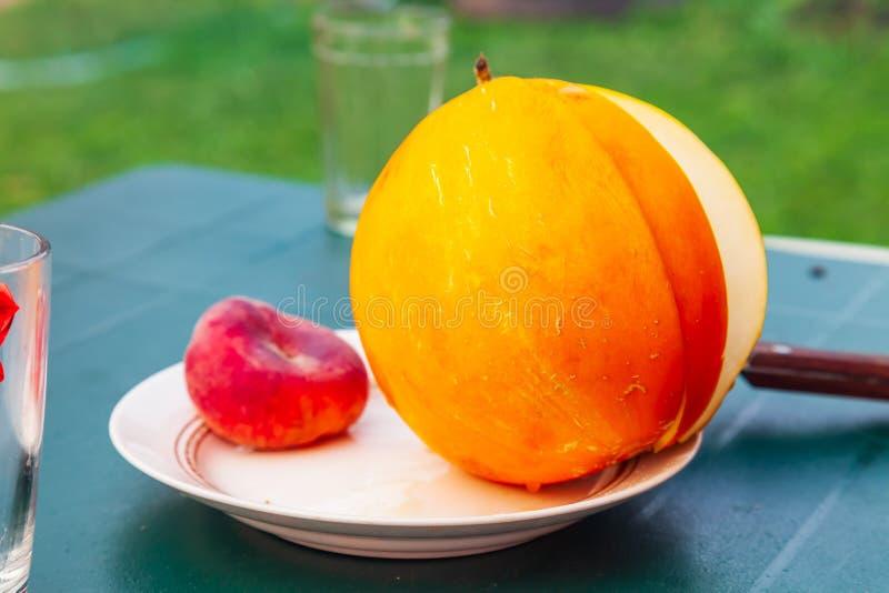 Свежая желтая дыня с частью отрезка лежит на белой плите на таблице Плоды и витамины для стоковые изображения rf
