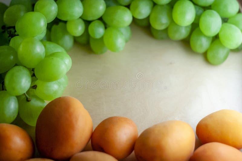 Свежая зеленая виноградина и зрелые абрикосы поверх деревянной текстурной поверхности Конец-вверх с космосом экземпляра стоковое изображение