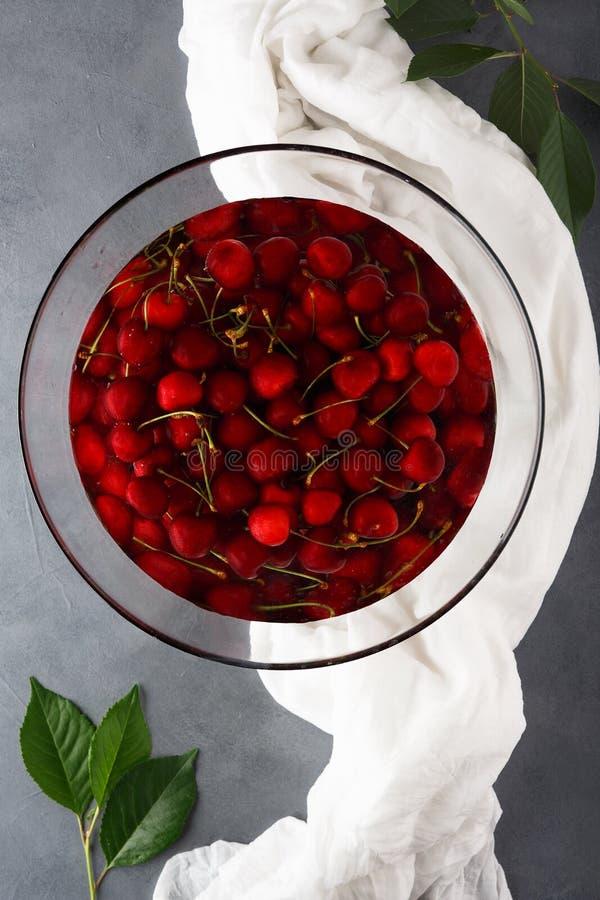 Свежая зрелая сладкая вишня в большом стеклянном шаре заполненном с чистой водой, концом-вверх стоковое изображение