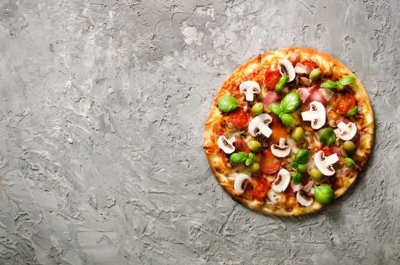 Свежая итальянская пицца с грибами, ветчина, томаты, сыр, оливка, базилик, на серой конкретной предпосылке, деревенская таблица э стоковое фото rf