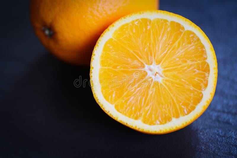 Свежая оранжевая половина предпосылки куска плода темной стоковое фото