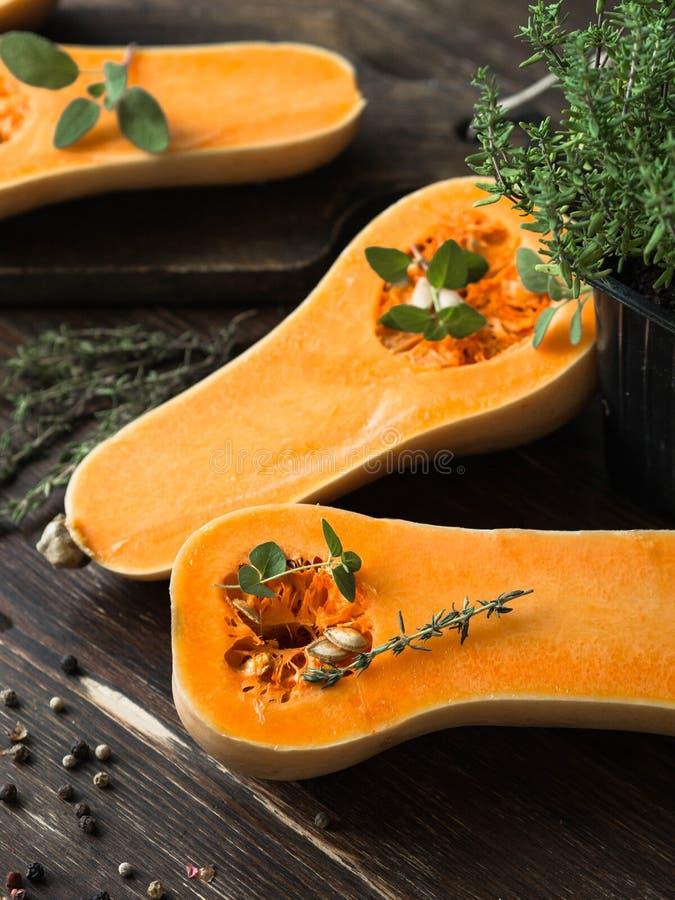 Свежая оранжевая тыква муската, отрезок в половинном, готовых для печь с специями и травами на деревянных доске и таблице стоковые изображения