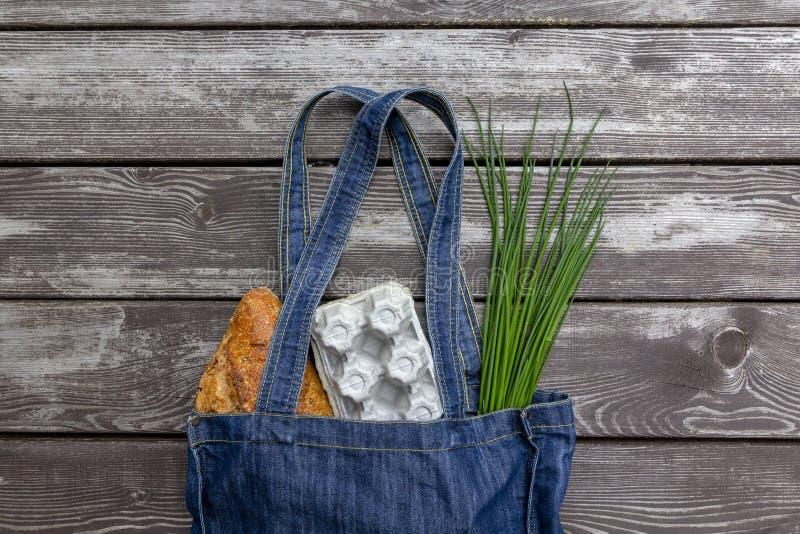 Свежая продукция в голубой сумке рынка джинсовой ткани на деревянной предпосылке, плоском положении Хозяйственная сумка Eco друже стоковые изображения