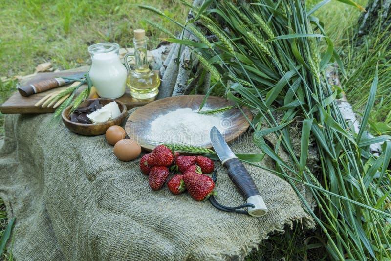 Свежая сочная органическая клубника с молоком, мукой, яичками и маслом на таблице стоковое фото