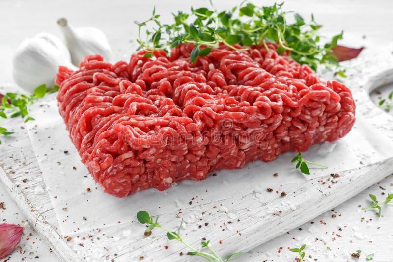 Свежая сырцовая говядина семенила мясо с солью, перцем, чилями и свежим тимианом на белой доске стоковое фото rf