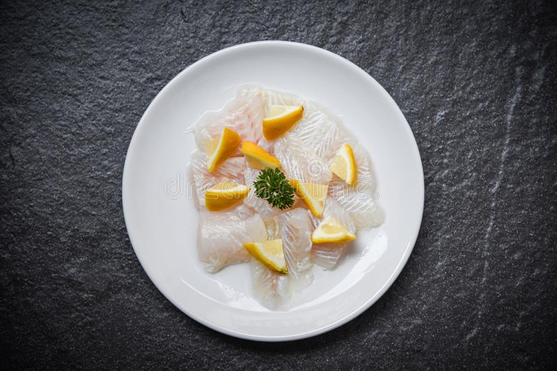 Свежая часть филе сырых рыб на белой плите с лимоном на темной предпосылке - мясе рыб тележки pangasius стоковое изображение