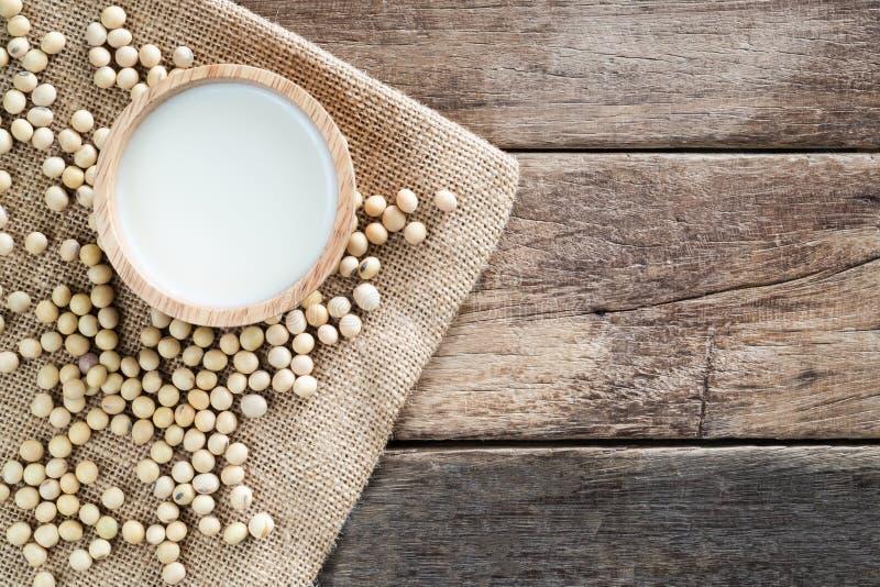 Свежее белое соевое молоко в деревянном шаре с фасолью сои на ткани мешка реднины стоковое изображение rf
