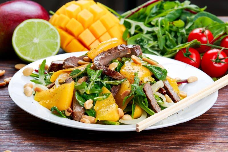 Свежее вкусное манго, салат говядины с овощами и гайки стоковое фото rf