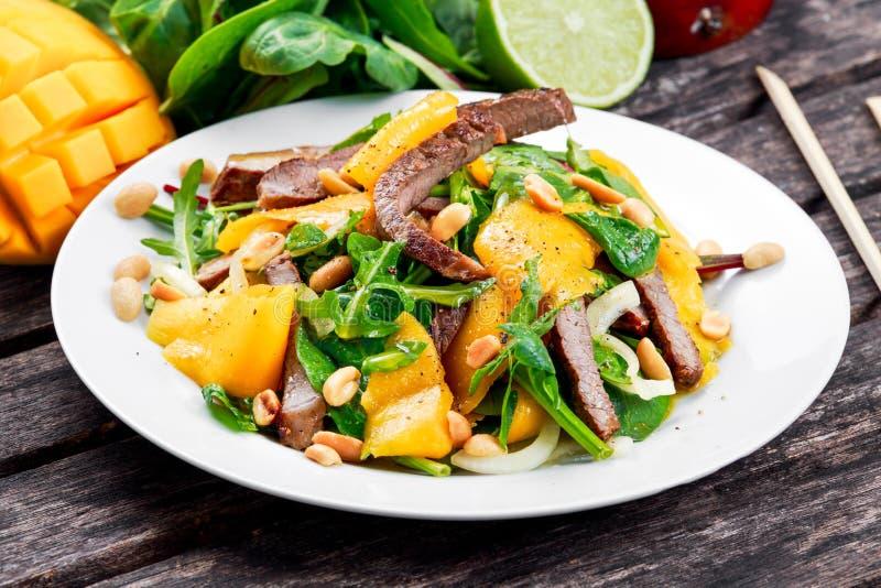 Свежее вкусное манго, салат говядины с овощами и гайки стоковая фотография rf