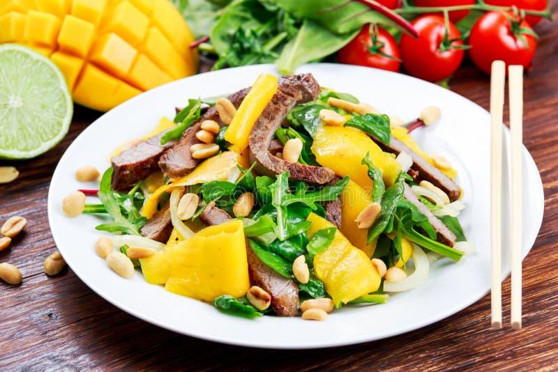 Свежее вкусное манго, салат говядины с овощами и гайки стоковое изображение