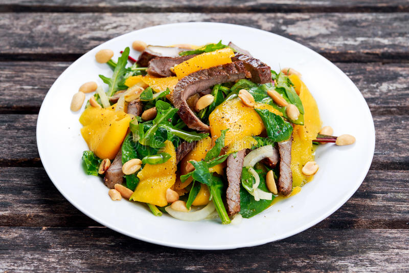 Свежее вкусное манго, салат говядины с овощами и гайки стоковая фотография