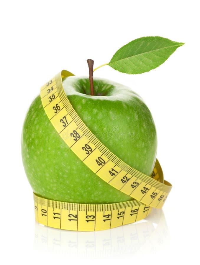 Свежее зеленое яблоко с желтой измеряя лентой стоковое фото