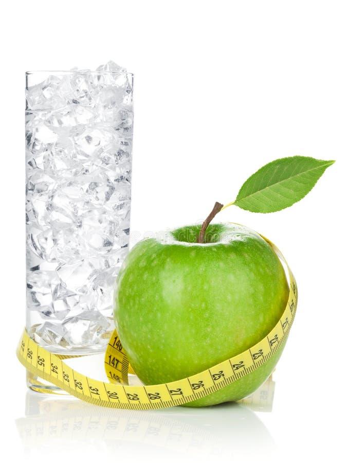 Свежее зеленое яблоко с желтыми измеряя лентой и стеклом воды стоковая фотография