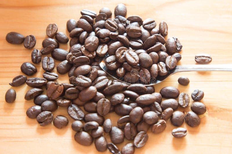 Свежее кофейное зерно после зажаренный в духовке на деревянной таблице стоковое фото