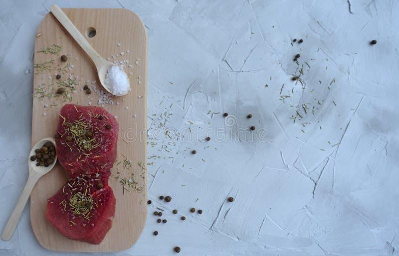 свежее мясо на деревянной доске со специями и солью готовыми для варить стоковое фото rf