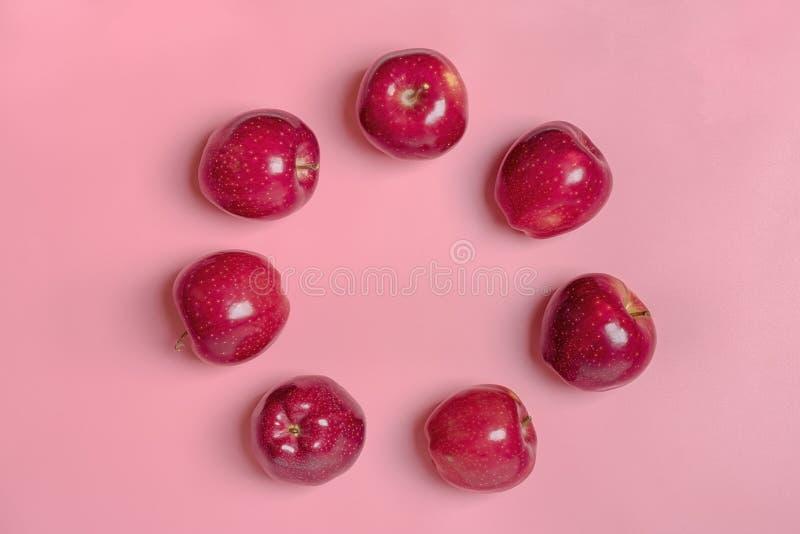 Свежее сжатое красное яблоко лежит на предпосылке пинка тенденции тысячелетней Плод с витамином C, кератин Естественное органичес стоковое изображение