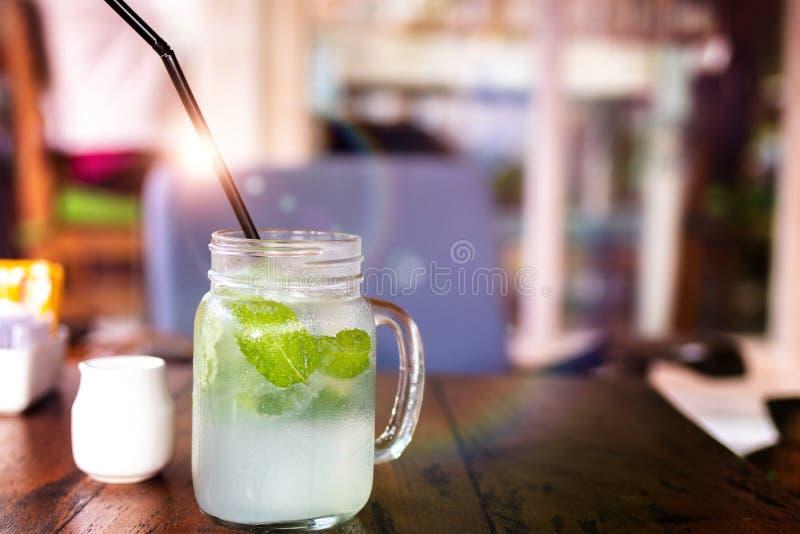 Свежее mojito лимонада питья на деревянном столе Mojitos с листьями мяты, известкой и льдом, внешними стоковое изображение