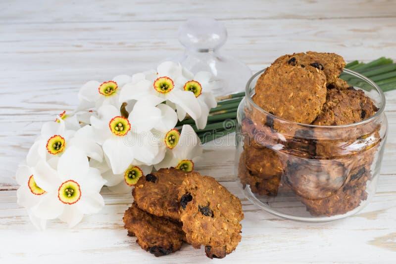 Свеже испеченные печенья изюминки овсяной каши и narcissus стоковое изображение