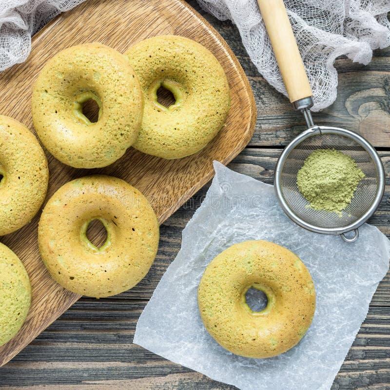 Свеже испеченные donuts банана matcha клейковины свободно на деревянной доске, взгляд сверху, квадратном формате стоковое фото