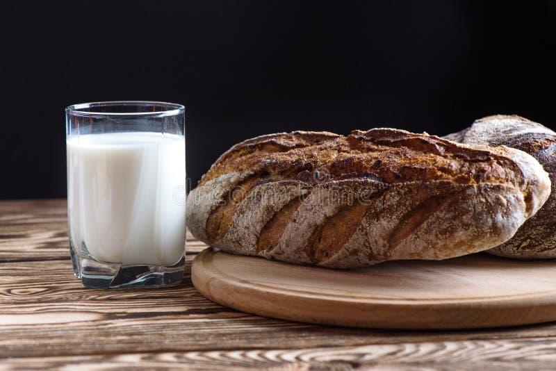 Свеже испеченный домашний хлеб лежит на круглой деревянной плите рядом с стеклом молока на черной предпосылке стоковые изображения