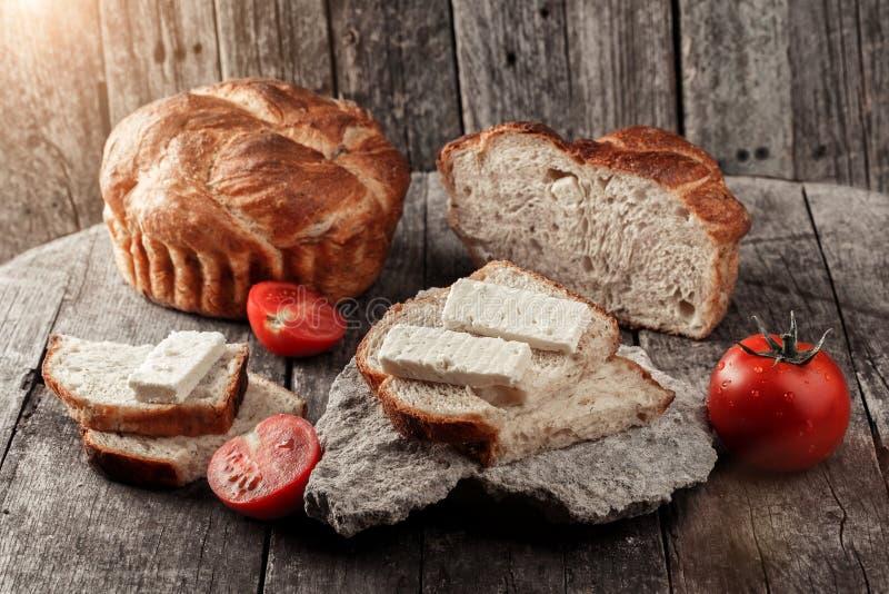 Свеже испеченный ломоть хлеба на деревенской деревянной предпосылке с сандвичем с сыром и томатами стоковое фото rf