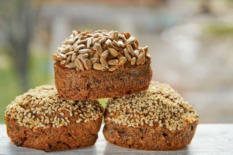 3 свеже испеченных торта изюминок при сезам и семена подсолнуха изолированные на деревянном столе 3 булочки на запачканной предпо стоковые изображения