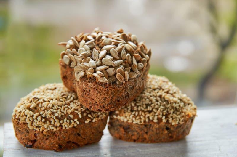 3 свеже испеченных торта изюминок при сезам и семена подсолнуха изолированные на серой таблице 3 булочки на предпосылке природы стоковые изображения