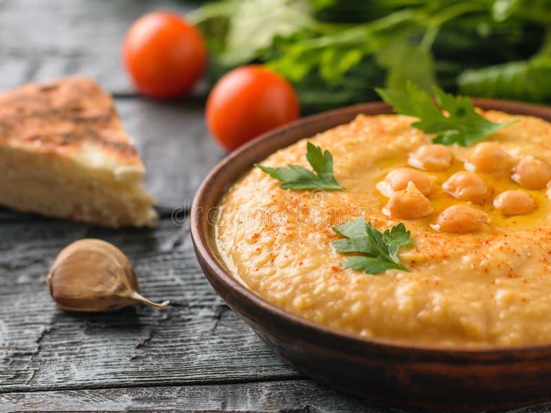 Свеже сделанное hummus в шаре глины на таблице с куском хлеба стоковые изображения