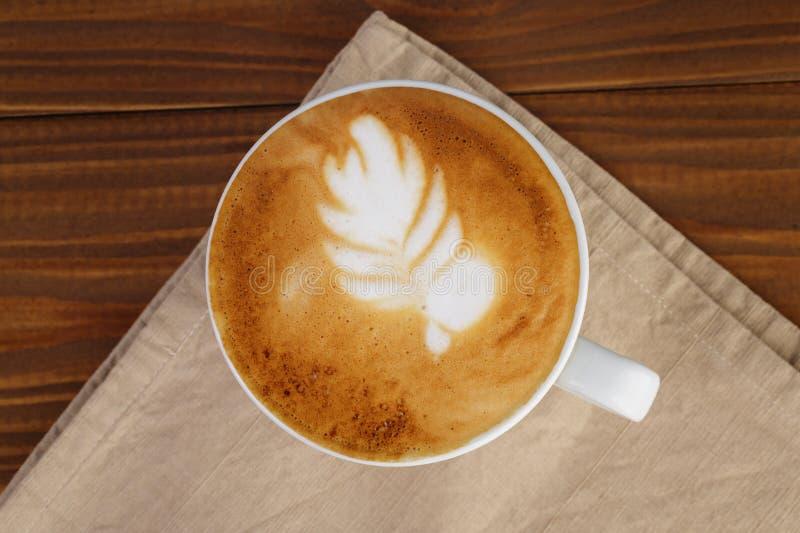 Свеже сделанная чашка капучино с искусством лист стоковые изображения