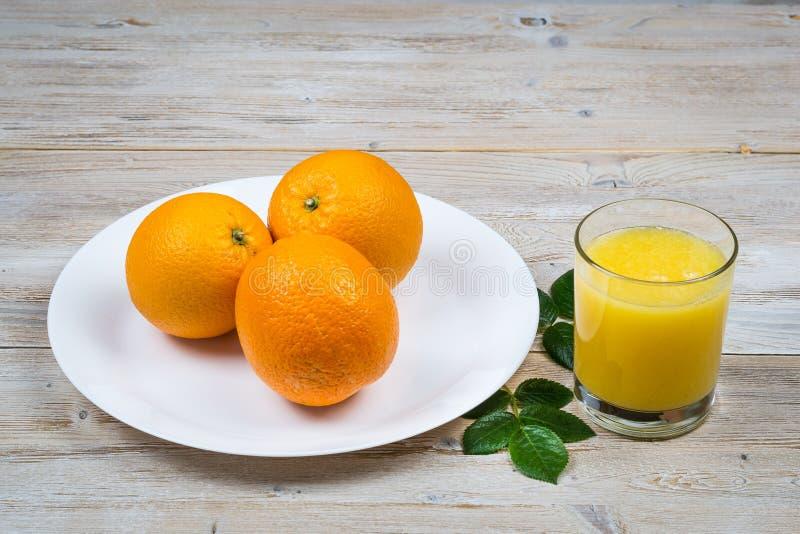 Свежие апельсины на белой плите на деревенских деревянном столе и стекле конца-вверх сока стоковые изображения rf