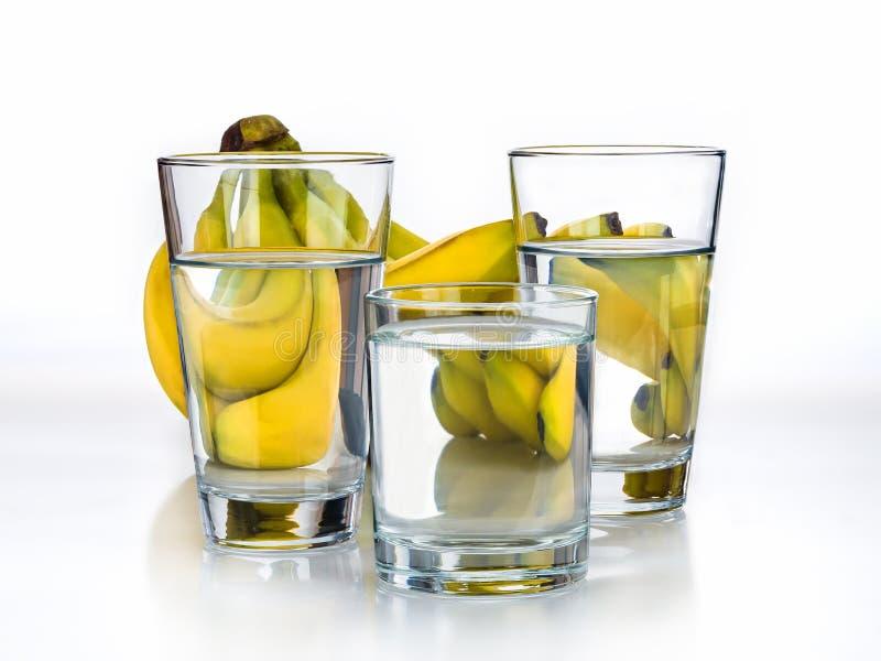 Свежие бананы и стекло воды на белой предпосылке стоковое изображение rf