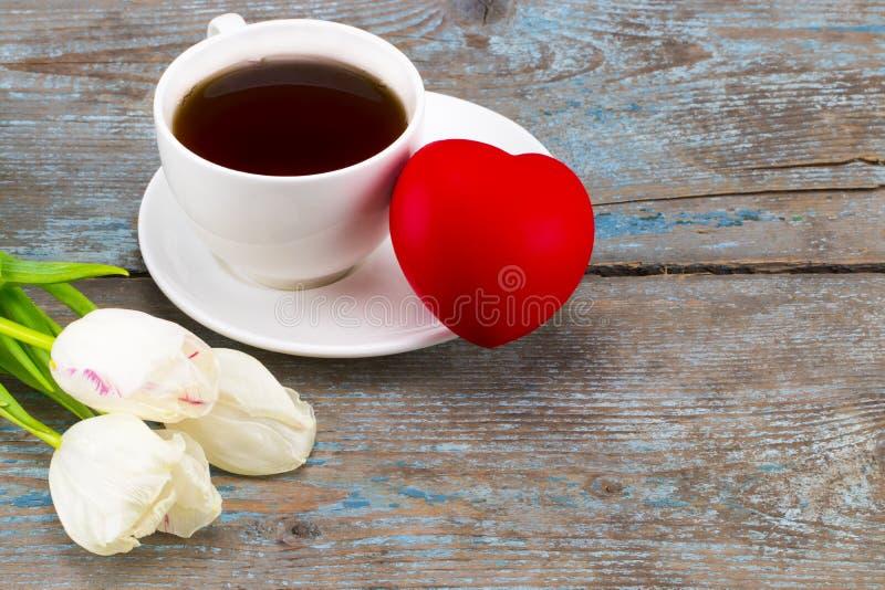 Свежие белые тюльпаны и кофейная чашка с сердцем над деревянным backgro стоковые изображения