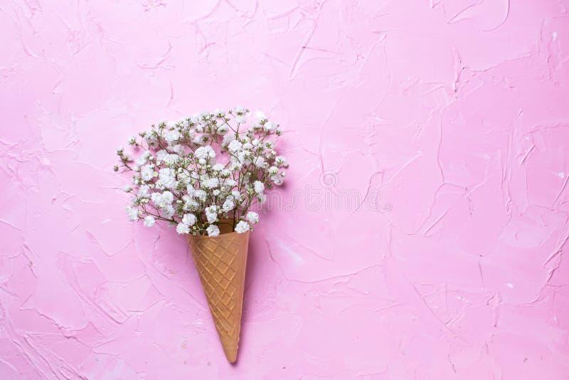 Свежие белые цветки gypsofila в конусе вафли на розовой текстурированной предпосылке стоковые изображения