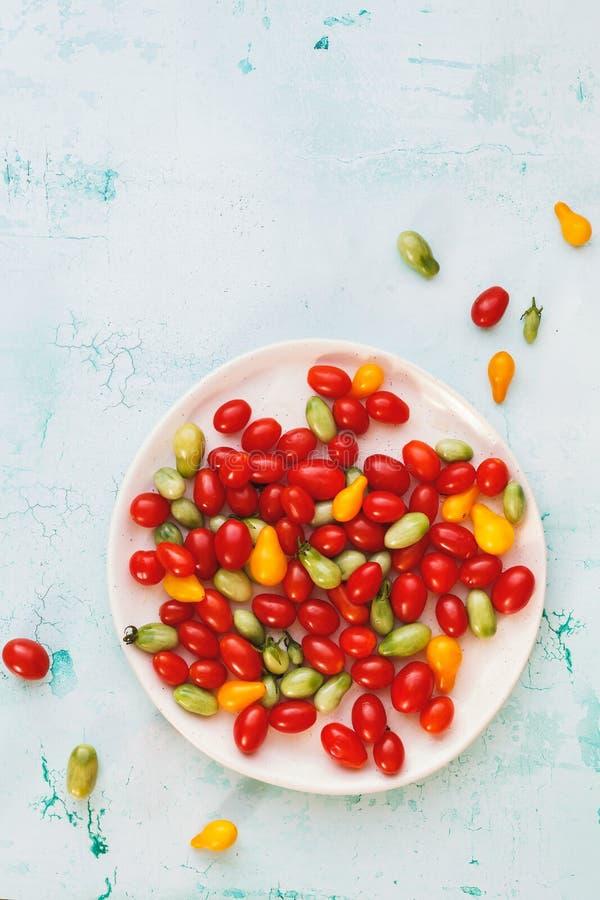 Свежие вишневые помидоры различных цветов на керамической тарелке стоковые изображения rf