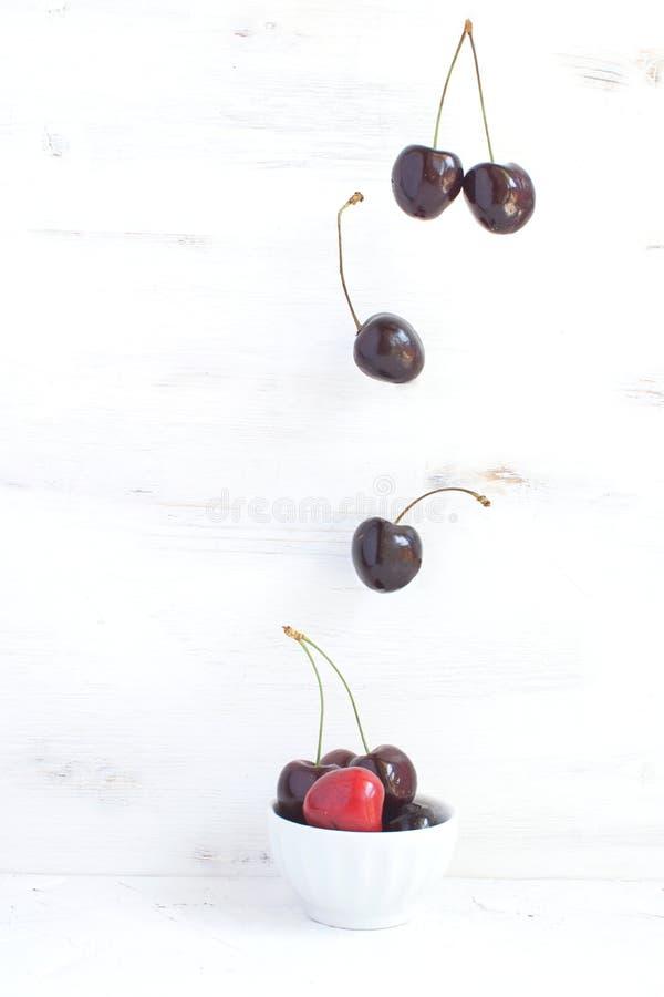 Свежие вишни в белом шаре фарфора с вишнями летания над плодом лета еды потери веса здоровым и концепцией ягод стоковое фото rf