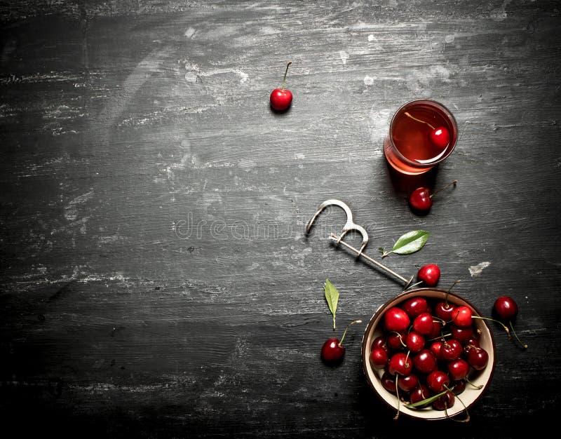 Свежие вишни в чашке и соке в стекле стоковые фотографии rf