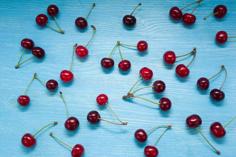 Свежие вишни разбросанные на деревянный стол стоковые фото