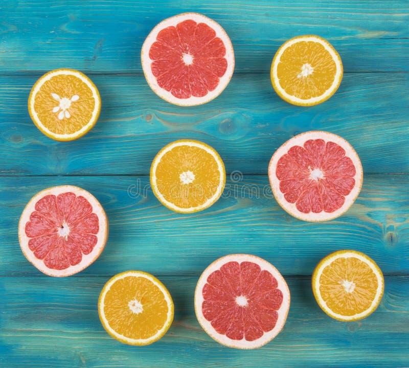 Свежие грейпфрут и апельсин неполной вырубки на голубой деревянной предпосылке стоковые изображения rf