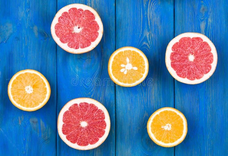 Свежие грейпфрут и апельсин неполной вырубки на голубой деревянной предпосылке стоковая фотография rf