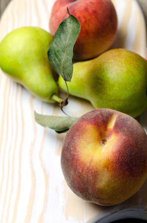 Свежие груши и персики на деревянной разделочной доске стоковое фото