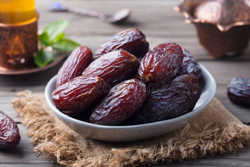 Свежие даты Medjool в шаре с чаем kareem ramadan Серая деревянная предпосылка стоковая фотография